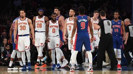 Knicks players look on against the Pistons during