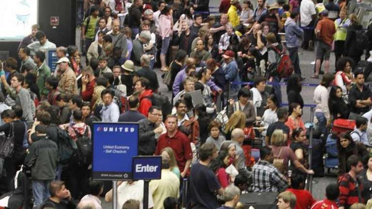 United Airlines passengers crowd the United ticketing area