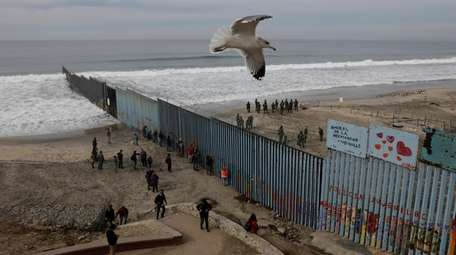 People look on from the Mexican side, left,