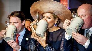Dutch Queen Maxima (C) drinks beer in a