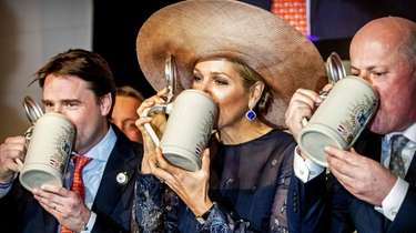 Dutch Queen Maxima (C) drinks beer in a