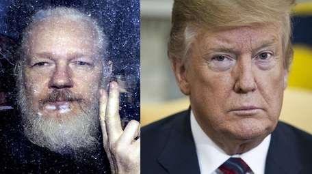 Julian Assange, left, gestures to reporters from a
