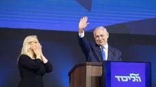 Israeli Prime Minister Benjamin Netanyahu waves as wife