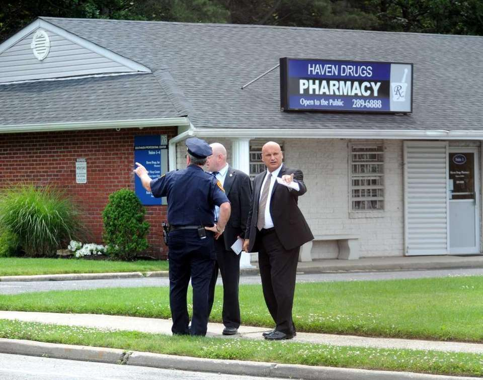 Suffolk homicide investigators stand near Haven Drugs on