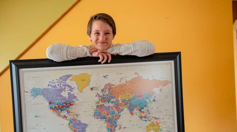 Paula Pecorella holds a world map, on which