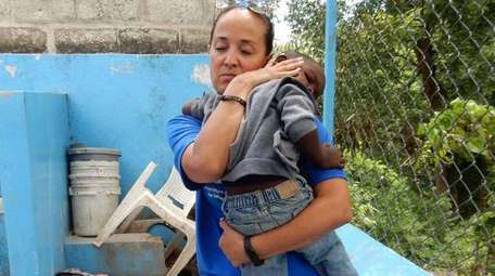 Melissa Correa Borger holds a young child in