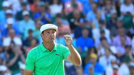 Bryson DeChambeau of the United States catches his