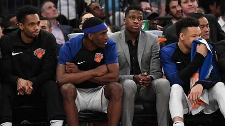 Knicks players look on from the bench late