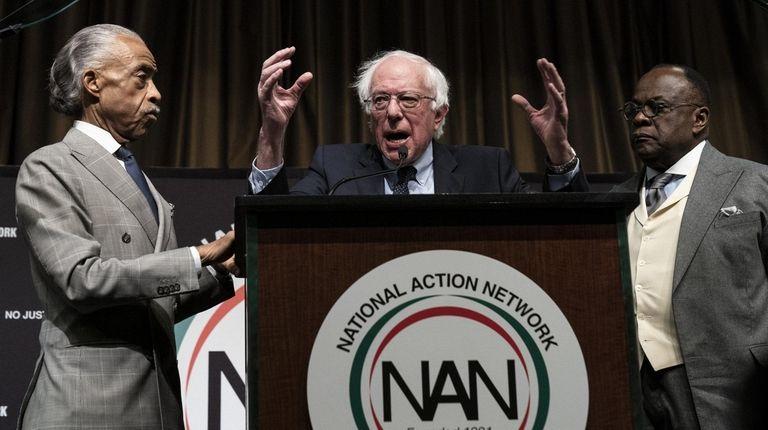 Democratic presidential hopeful Sen. Bernie Sanders is flanked