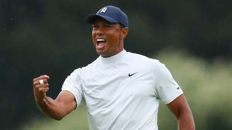 Tiger Woods reacts to his birdie putt on