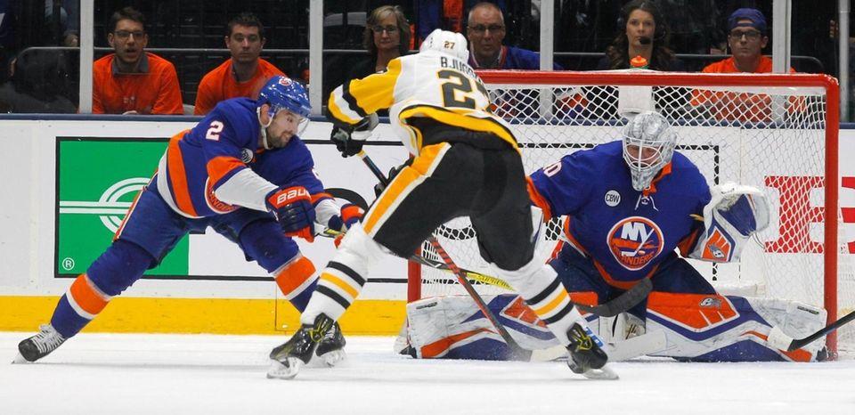 Islanders defenseman Nick Leddy (2) and Islanders goaltender