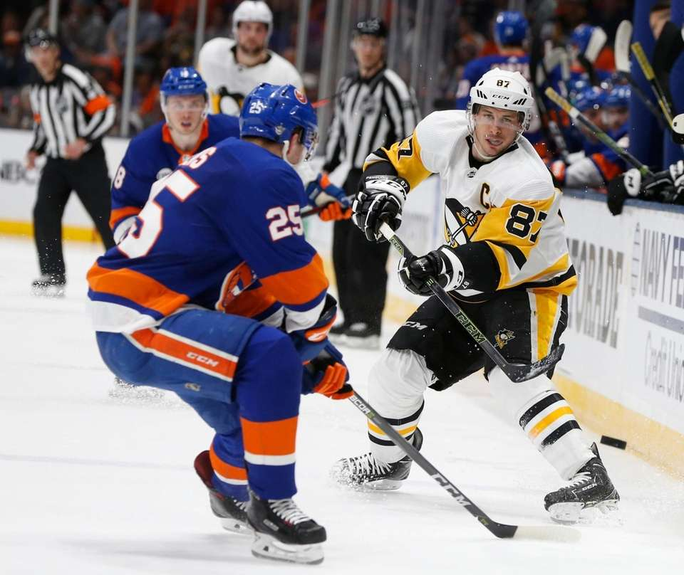 Islanders defenseman Devon Toews (25) defends Penguins center