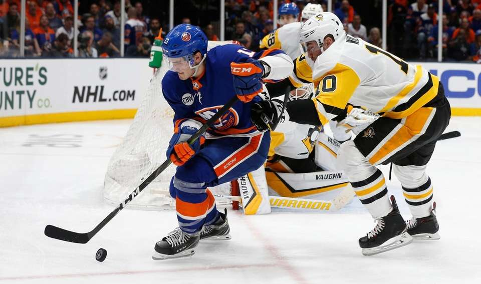 Islanders center Mathew Barzal (13) is defended by