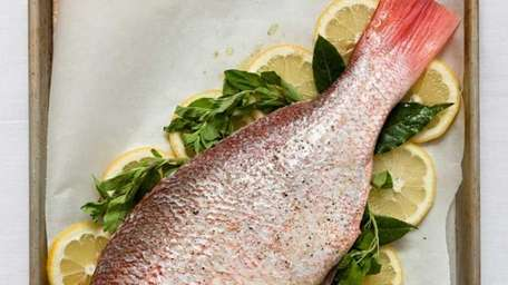 A whole red snapper is roasted with sliced