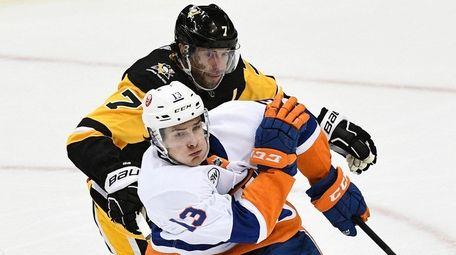 Islanders center Mathew Barzal skates the puck out