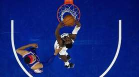 The Nets' Caris LeVert, right, dunks the ball
