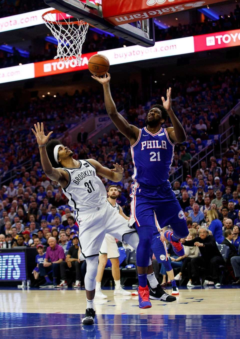 The 76ers' Joel Embiid, right, puts up the