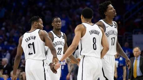 The Nets' Caris LeVert, center left, celebrates with