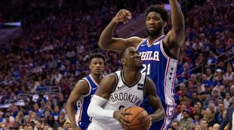 The Nets' Caris LeVert, left, drives to the