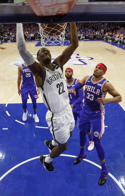 The Nets' Caris LeVert, left, dunks the ball