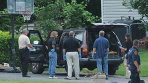Investigators inspect a vehicle in driveway of home