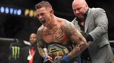 Dustin Poirier celebrates after recieving the title belt