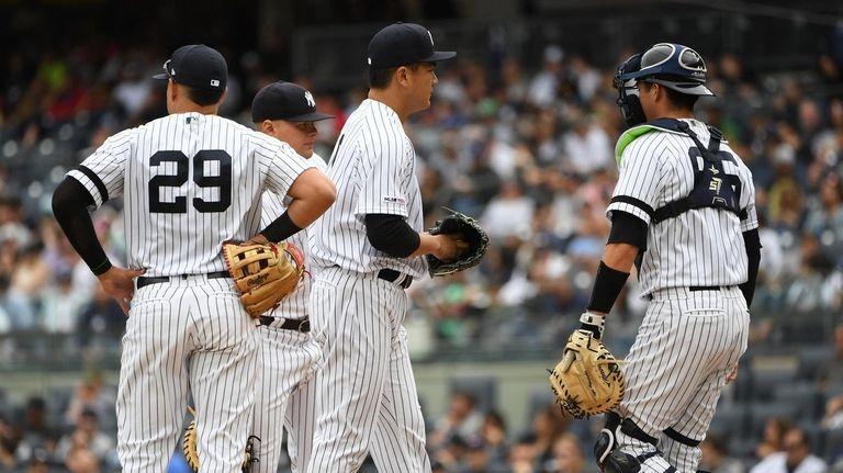 Yankees' Masahiro Tanaka stands on the mound as