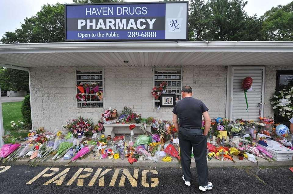 Mourners pay their respects at Haven Drugs pharmacy,