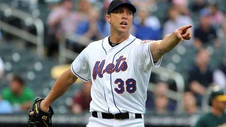 Mets starting pitcher Chris Capuano points in the