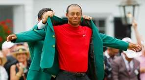 Tiger Woods is awarded the green jacket by