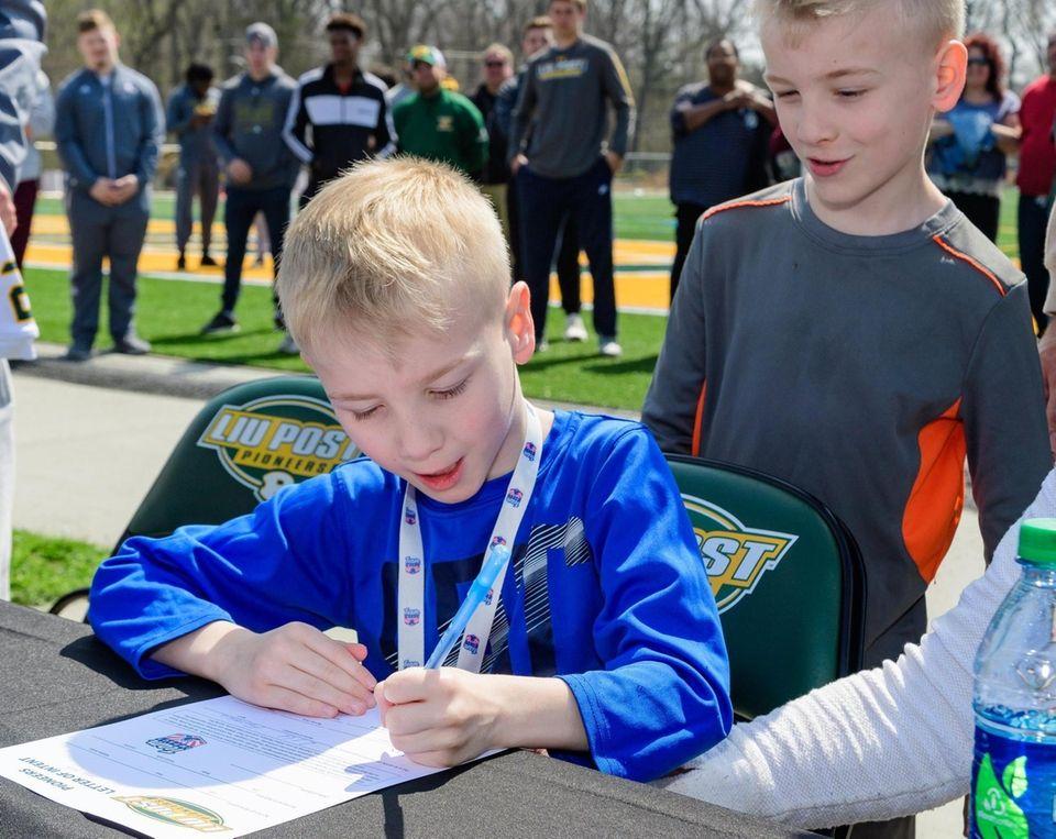Team IMPACT participant Max Von Holt signs his