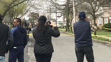 Onlookers take photos of the plane on Clarendon