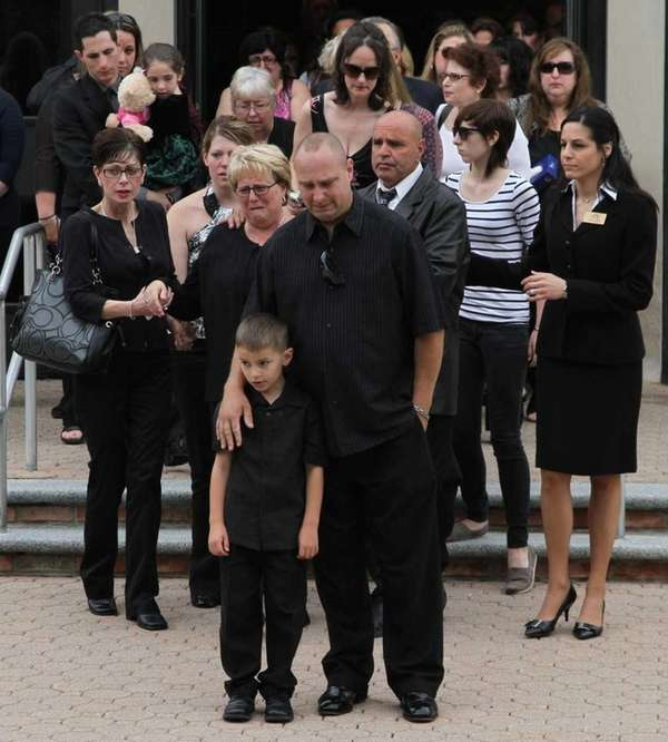 Mourners watch as the coffin of Jaime Taccetta,