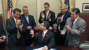 New York Gov. Andrew M. Cuomo hands pens