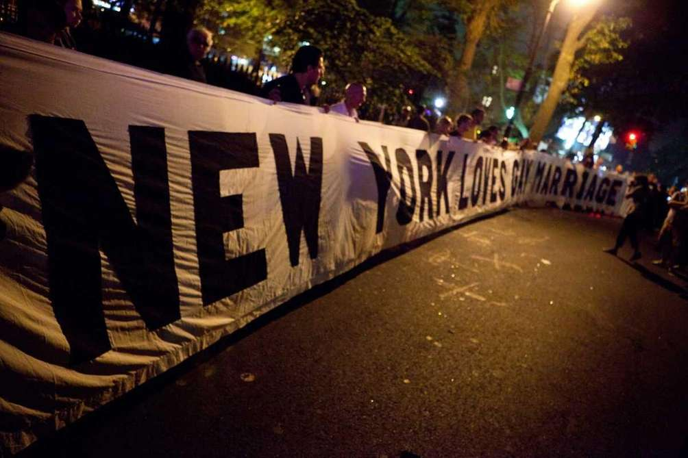 Revelers bring out their banner to celebrate the