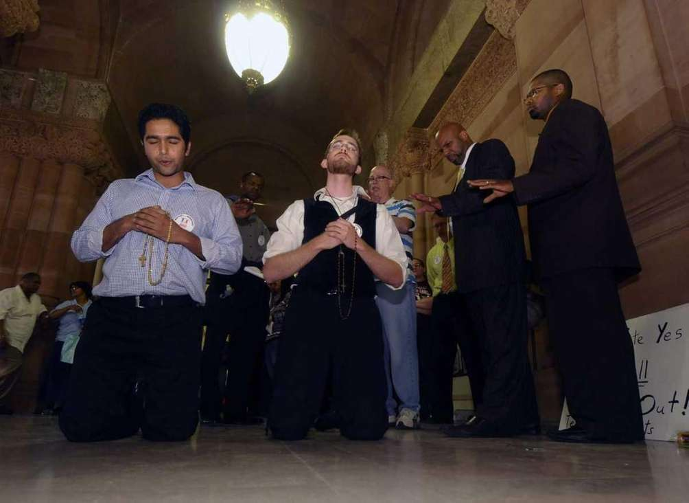 Opponents of same sex-marriage pray after Senate members