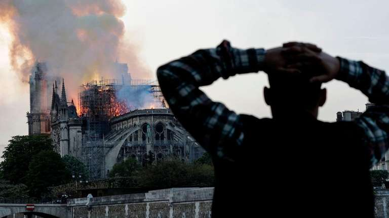 A man watches the landmark Notre-Dame Cathedral burn,