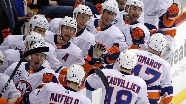 Islanders' Leo Komarov (47) leads the way back