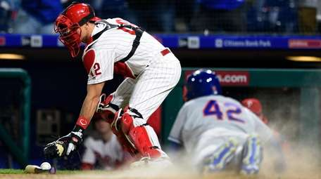 Phillies catcher J.T. Realmuto, left, is unable to