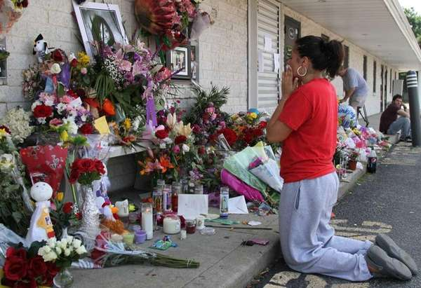 Kimberly Jimenez kneels outside Haven Drugs. (June 26,