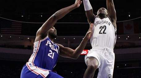 Brooklyn Nets' Caris LeVert, right, goes up to