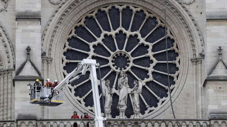 Firefighters outside one of Notre Dame Cathedral's rose