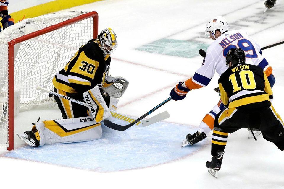 The Islanders' Brock Nelson puts a shot behind