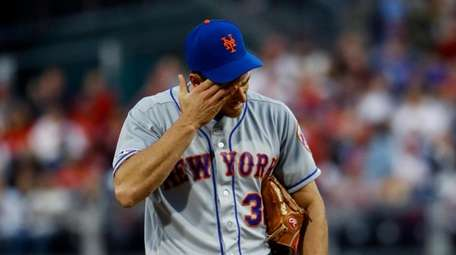 Mets' Steven Matz wipes his face after hitting