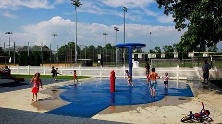 Kids take advantage of the sprinkler in the