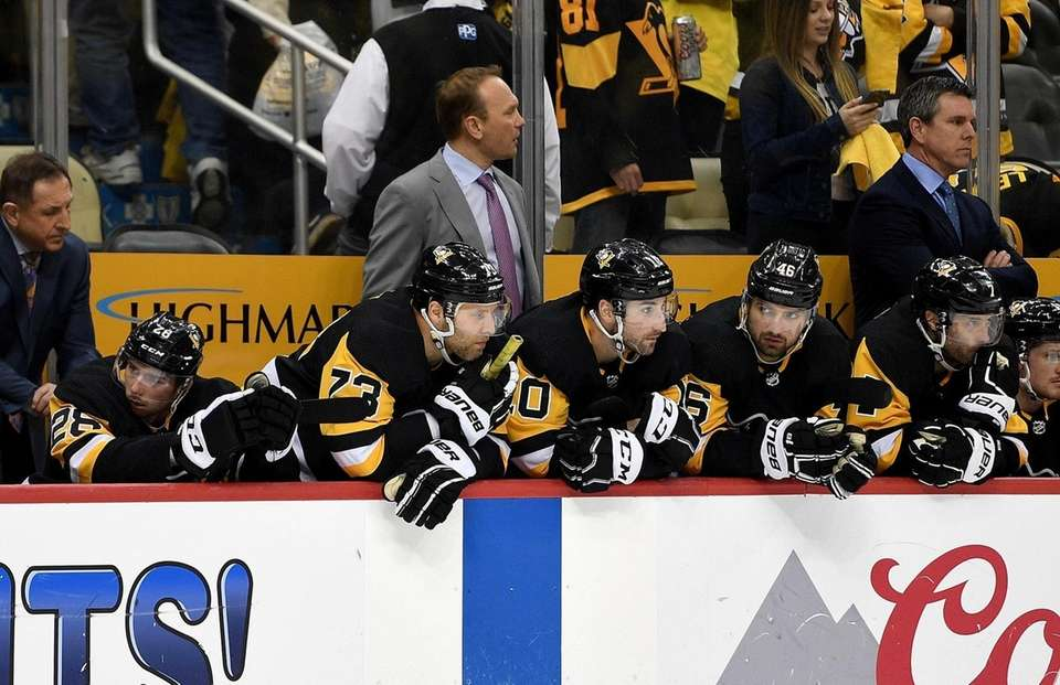 Members of the Penguins look on from the