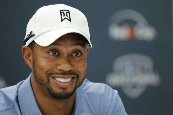 Tiger Woods smiles during a news conference at