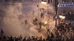 Demonstrators run away from tear gas during a