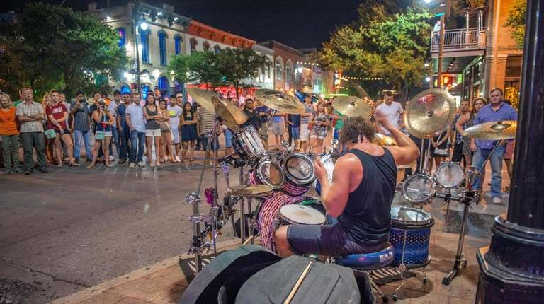 A street musician entertains a crowd on Sixth