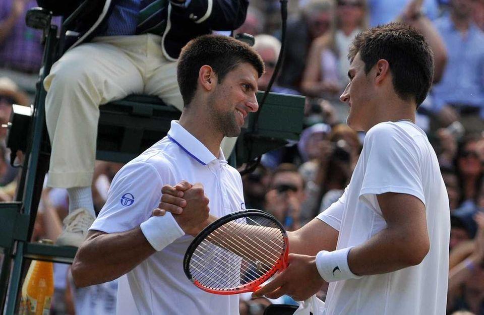 Serbian player Novak Djokovic (L) shakes hands after